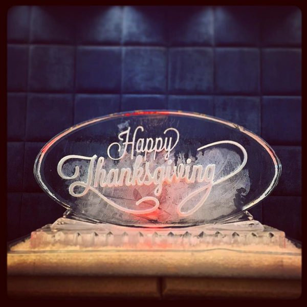 Oval ice sculpture etched with Happy Thanksgiving on the front