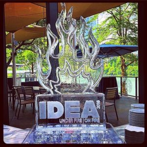 Ice Sculpture in the shape of fire on top of pedestal etched with IDEA by Full Spectrum Ice Sculptures
