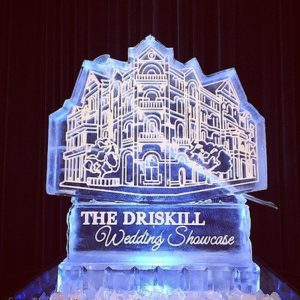 Large ice luge in the shape of The Driskill hotel on a pedestal with the words The Driskill Wedding Showcase etched on it, by Full Spectrum Ice Sculptures
