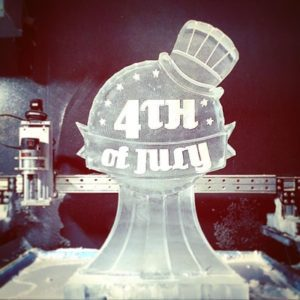 Single block ice sculpture on pedestal with 4th of July etched on the front and topped with a tiny hat; by Fully Spectrum Ice Sculptures