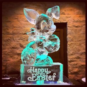 Easter Bunny shaped ice sculpture sitting on a pedestal with Happy Easter etched on it by Full Spectrum Ice Sculptures