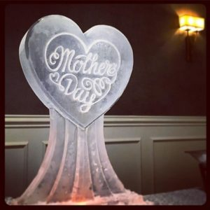 Mother's Day ice sculpture in the shape of a heart on a pedestal by Full Spectrum Ice Sculptures