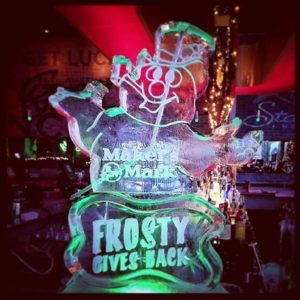 "Frosty the Snowman Ice Luge sitting on a pedestal with ""Frosty Gives Back"" for Makers Mark party by Full Spectrum Ice Sculptures"