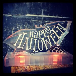 "Bat shaped ice sculpture with ""Happy Halloween"" etched on the back by Full Spectrum Ice Sculptures"