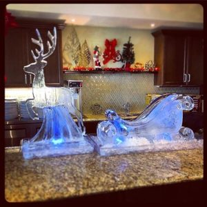 Ice Sculpture in the shape of a reindeer with a sleigh for holiday display by Full Spectrum Ice Sculptures