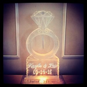 Diamond Ring shaped ice sculpture on pedestal with etching of names and date by Full Spectrum Ice Sculptures