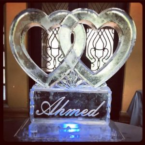 2 Interlocked hearts made of ice on an ice pedestal etched with a name by Full Spectrum Ice Sculptures