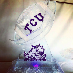 Football shaped ice luge with TCU carved on the side and colored in Purple, with TCU mascot on the pedestal; by Full Spectrum Ice Sculptures; Serving Austin to San Antonio